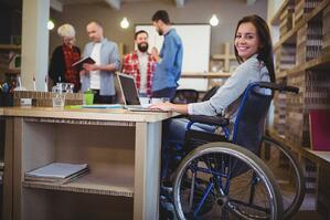 confident disabled businesswoman using laptop in office